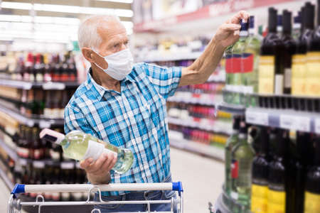 older european man wearing mask with covid protection chooses bottle of alcohol in supermarket