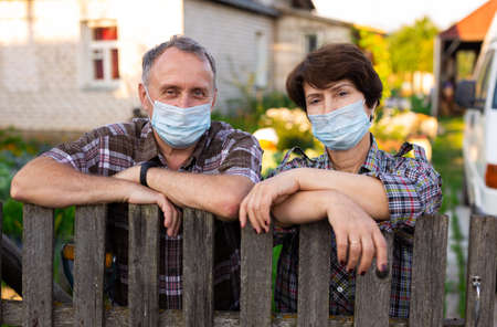 Portrait of two farmers wearing protective masks at the fence of their country house Stok Fotoğraf