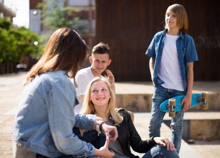 group of teenagers communicate in schoolyard