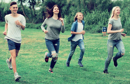 group of teenagers running through green lawn in summer in park