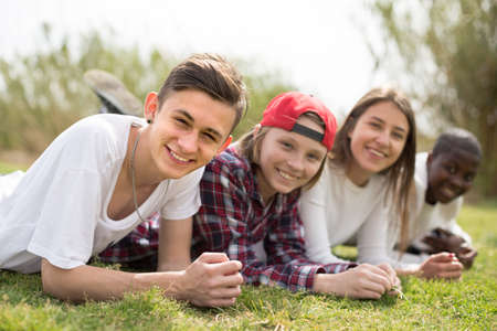 group of multinational modern teens lie in the park on the grass