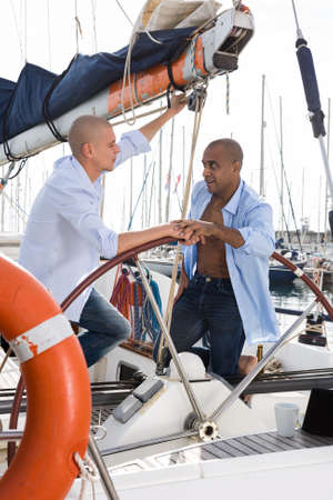 Two men A couple of guys in blue shirts chatting on private sailing yacht in seaportin blue shirts sitting on sailing yacht in the port