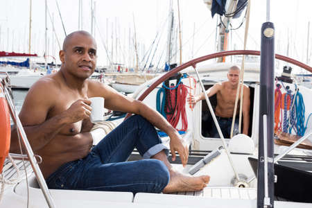 Latin American with a cup of coffee in his hand sitting on the deck of a yacht in the seaport