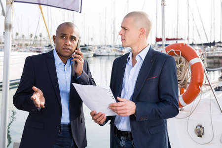 two male businessmen agree on a deal at the seaport
