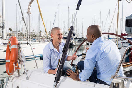 Two men in blue shirts sitting on sailing yacht in the port
