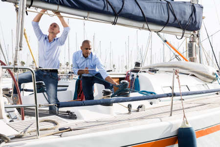 Two young men in blue shirts tidy up private sailing yacht in the seaport