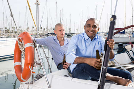 Two young men in blue shirts have a nice time on a private sailing yacht in the seaport