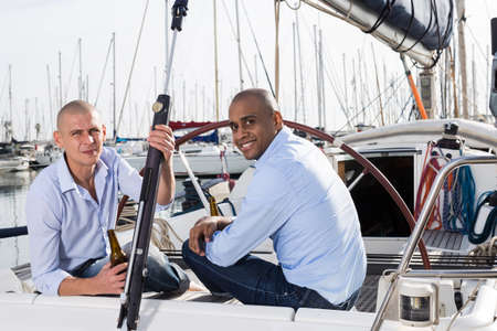 Two men in blue shirts relaxing on sailing yacht in the port