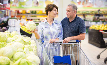 Mature couple husband and wife choose cabbagehead in the vegetables section of the supermarket Imagens