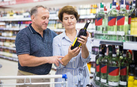 Mature family of retirees examines a bottle of vermouth in the alcohol section of a supermarket