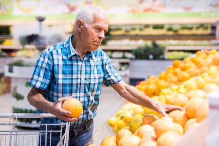 old age man choosing oranges and grapefruits in supermarket
