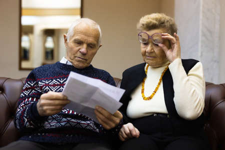 elderly couple man and woman are sitting on sofa in lobby of theater and looking at ticket