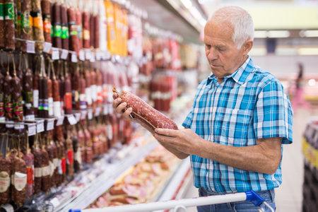 mature senor choosing uncooked smoked sausages in sausage department supermarket