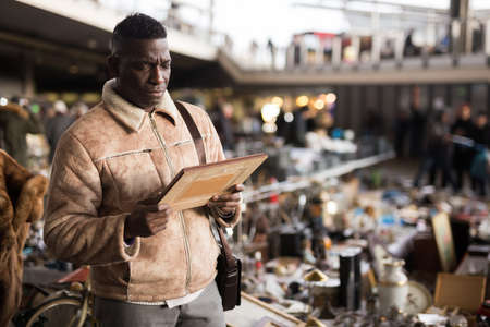 AfricaAmerican man chooses antiques on the flea market Stock Photo