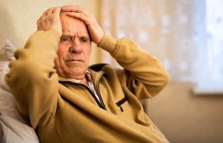 old man winces with headache due to noise