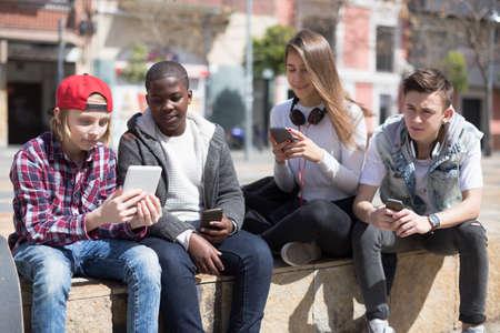 group of multinational teenagers play in smartphones in schoolyard
