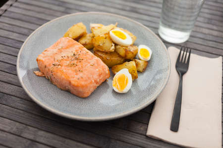 steamed salmon fillet with potato wedges and quail egg Standard-Bild