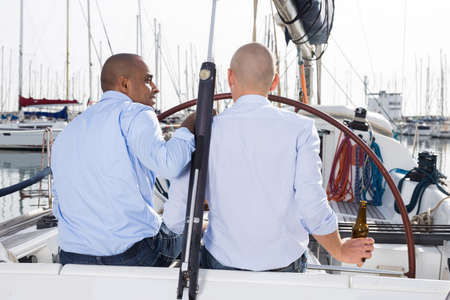 A couple of guys in blue shirts chatting on private yacht in the port Standard-Bild