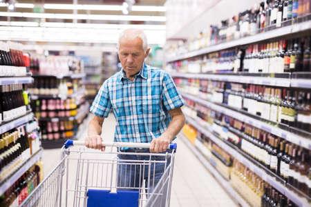 mature senor choosing alcoholic drinks in supermarket