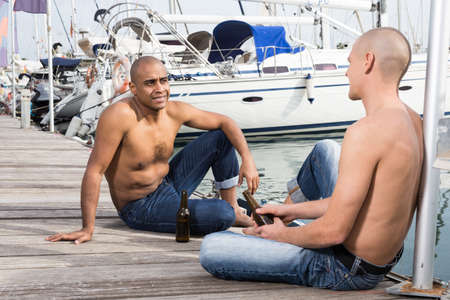 romantic couple of young men sitting and relaxing together on the pavement in the port