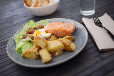 baked salmon fillet with fried potato wedges, homemade guacamole and quail eggs halves