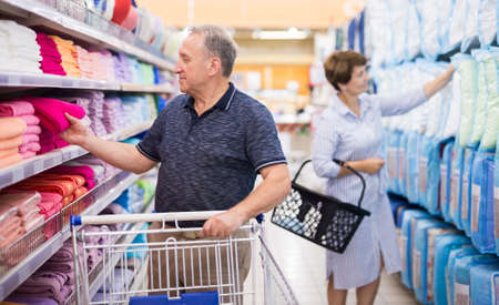 Mature man examines towels in linen department of the supermarket