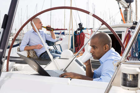 Latin American guy with laptop on private yachts in the seaport