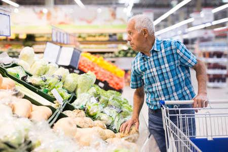 Elderly retired man buying turnip in grocery department of supermarket