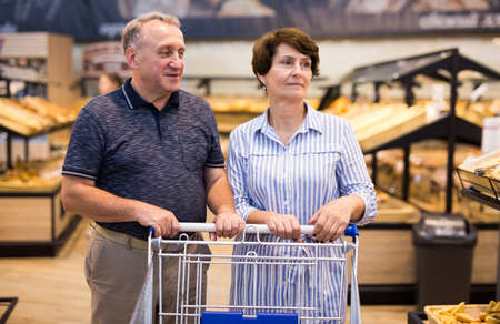 Mature family of retirees examines bread and pastries in grocery section of a supermarket
