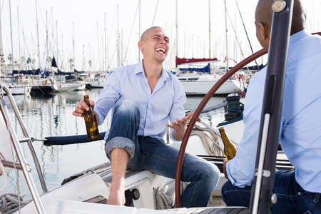 Two men in blue shirts and jeans with bare legs drinking beer and having fun on a yacht in the port