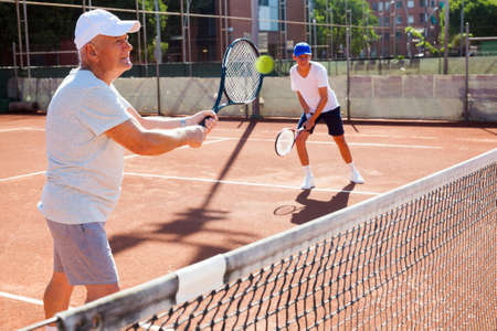 mature man and young man playing tennis court