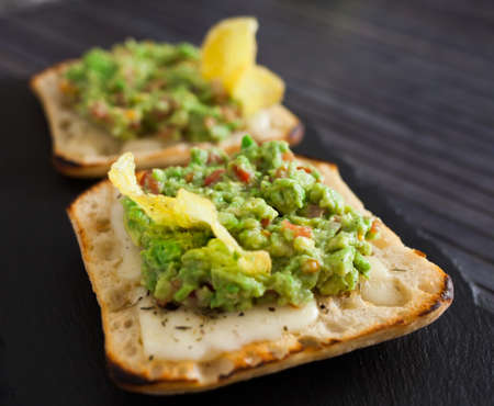 toasted slices of square bread with warm cheese and homemade guacamole on plate for healthy breakfast Standard-Bild