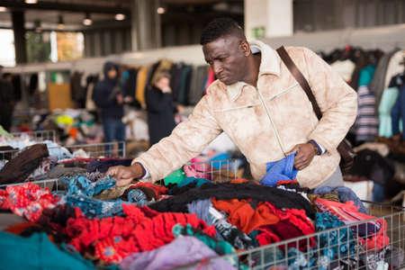 ordinary Afro-American guy considers sacond hands clothes on flea market Standard-Bild