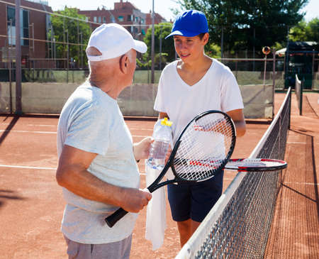 older man and young man talking on court playing tennis Standard-Bild