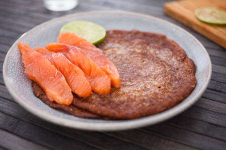 salted salmon fillet with buckwheat pancakes and lime