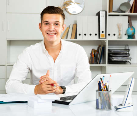 young guy in white shirt works in office and smiling