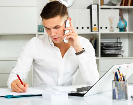 young guy in white shirt works at table with laptop and talking on phone in office