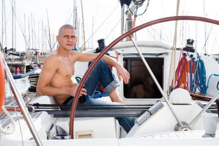 caucasian man topless with a bottle of beer in his hand sits on the deck of a yacht in seaport
