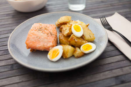 baked salmon fillet with fried potato wedges and quail eggs halves