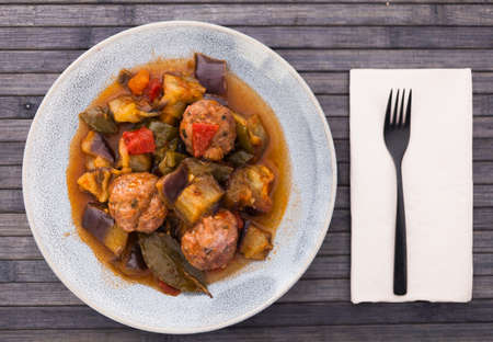 top view of plate of cooked meatballs with stewed eggplant in bowl Standard-Bild