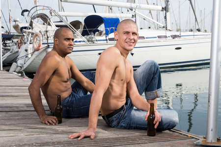 two guys without shirts in jeans sitting and relaxing near yachts in the port Standard-Bild