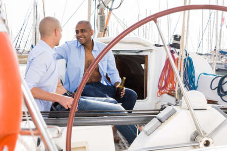 Two men A couple of guys in blue shirts chatting on private sailing yacht in seaportin blue shirts sitting on sailing yacht in the port Standard-Bild