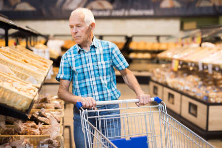 old age senor examines bakery products in the grocery section of the supermarket