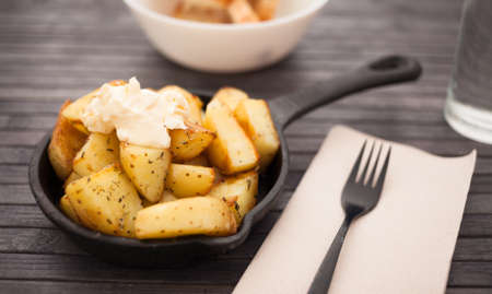golden fried potatoes with mayonnaise on small cast iron skillet