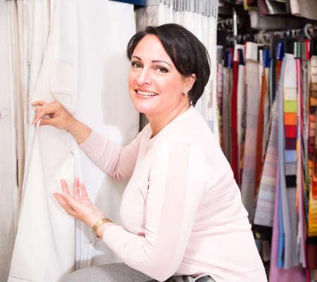 European woman customer, chooses light curtains for home decor