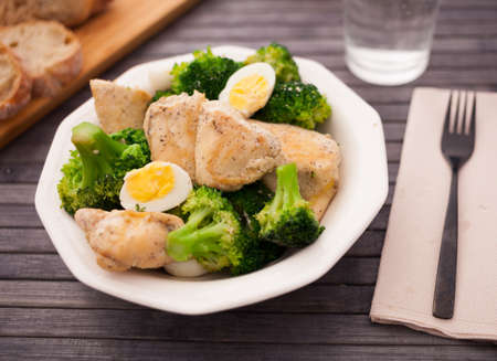 healthy appetizer of chicken pieces with broccoli and quail eggs in bowl for healthy lunch