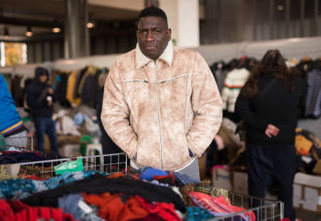 african american seller in a flea market is waiting for buyers