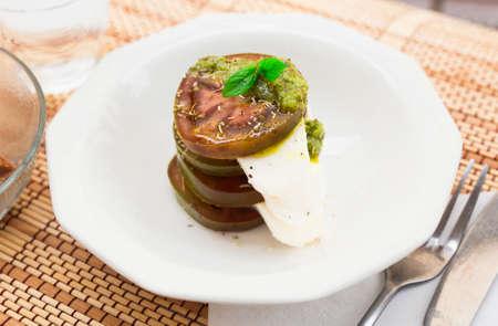 fresh caprese salad with mozzarella, black tomatoes and pesto in white plate