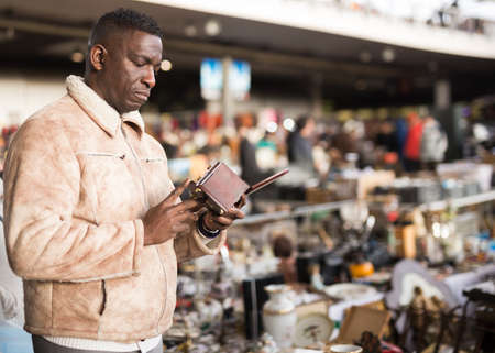 AfricaAmerican man chooses antiques on the flea market
