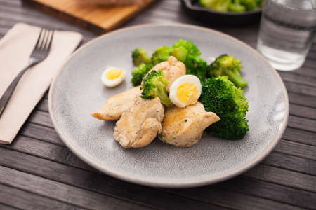 pieces of fried chicken breast with boiled broccoli and quail eggs on plate for lunch